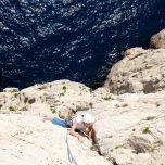 Les clapots légers de l'eau contre le calcaire changent le silence en un murmure tandis que Michel atteint le relais de la deuxième longueur